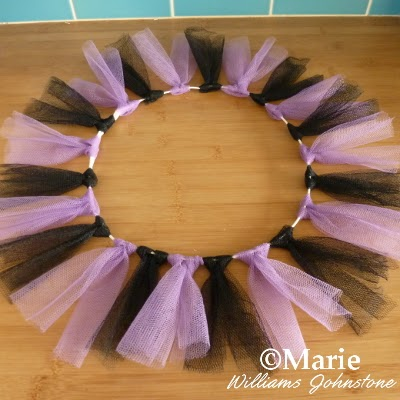 Black and purple tulle strips tied to a wire wreath frame