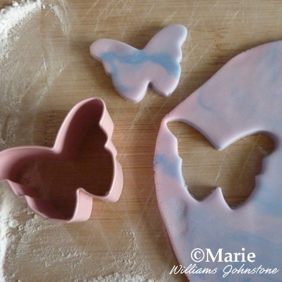 Cutting butterfly shapes out of fondant icing to make toppers for cupcakes butterflies lilac purple blue icing