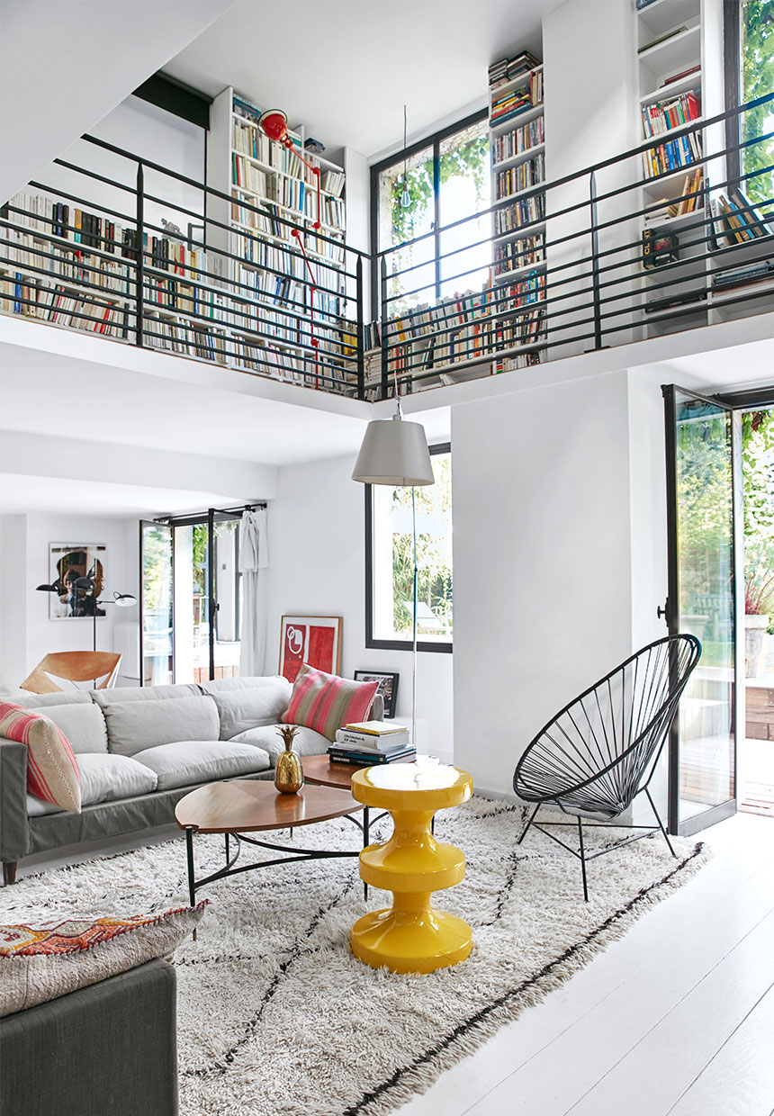 luxury large family villa with mid century modern design and large bookcase, gray sofa and yellow stool