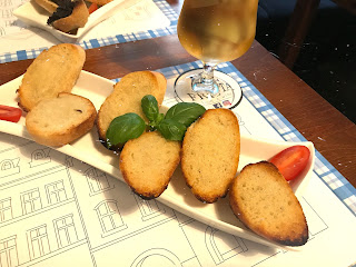 garlic bread on a plate with a beer next to it