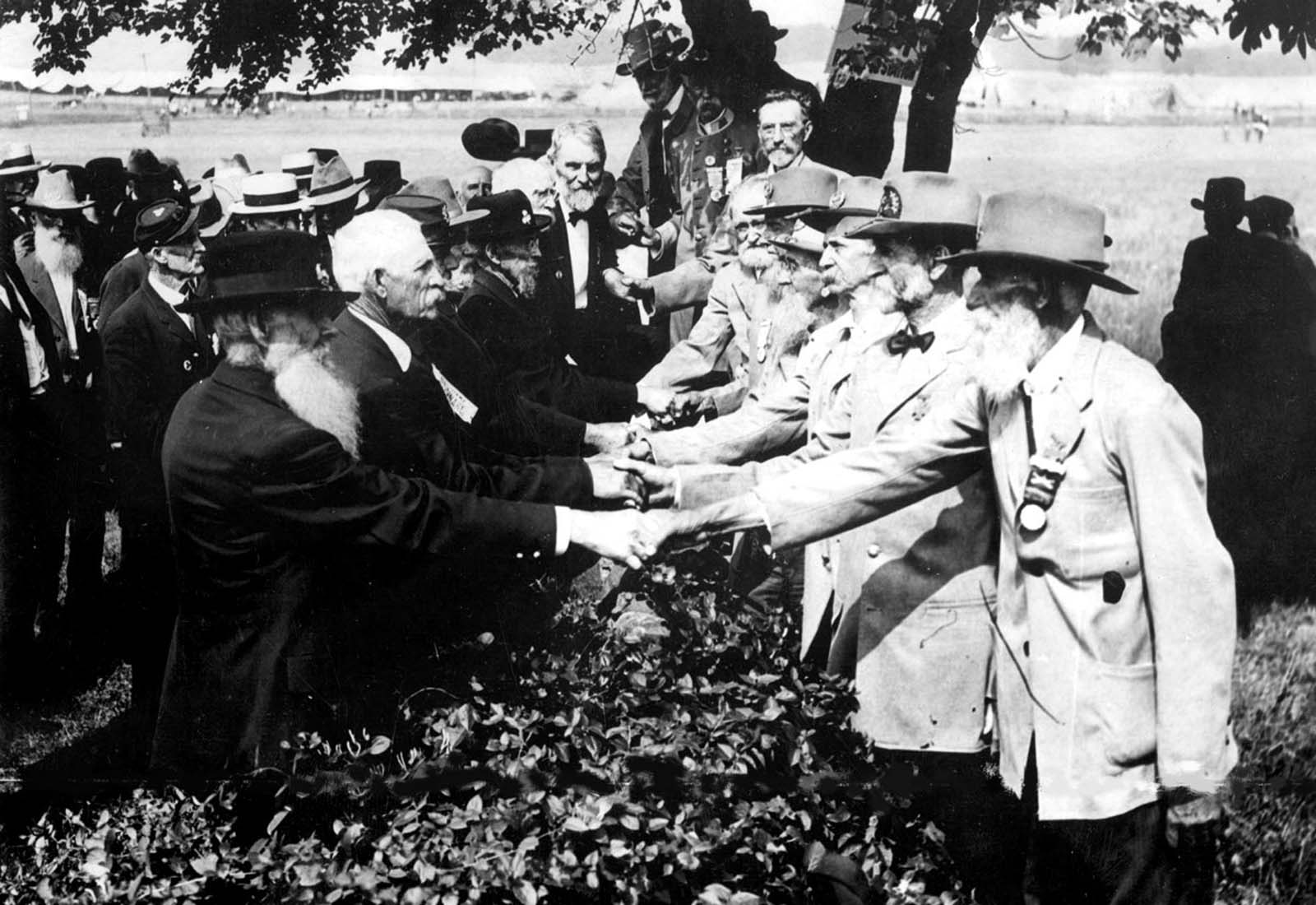 At the 50th anniversary of the battle of Gettysburg, Union (left) and Confederate (right) veterans shake hands at a reunion, in Gettysburg, Pennsylvania. 1913.