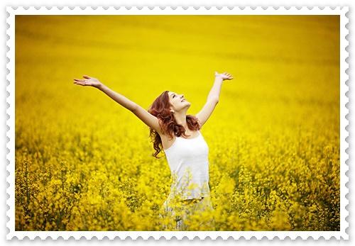 Olhando para o alto, uma jovem sorridente, de braços abertos, num campo florido, brilhantemente iluminado pela luz solar.