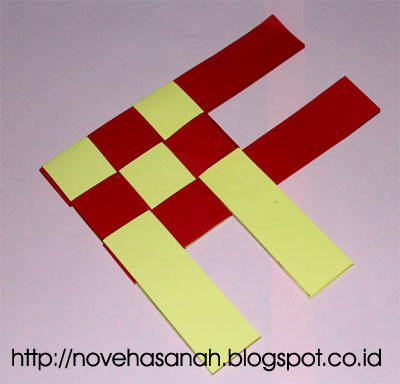 kita selanjutnya menyisipkan sisa ujung kertas merah ke bawah pita kertas warna kuning untuk mengunci anyaman kertas bekas ini