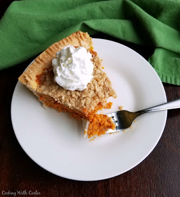 piece of carrot pie topped with whipped cream, first bite on fork