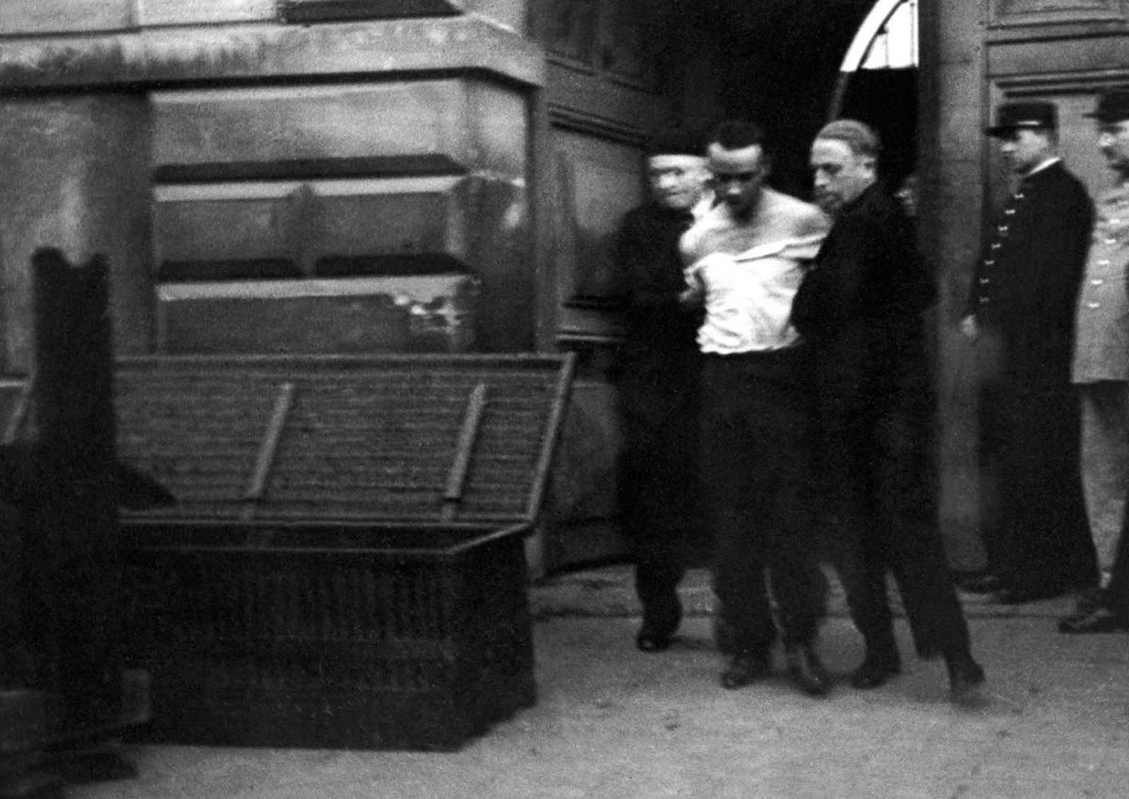 Weidmann is led to the guillotine, passing by the trunk that will be used to transport his body.