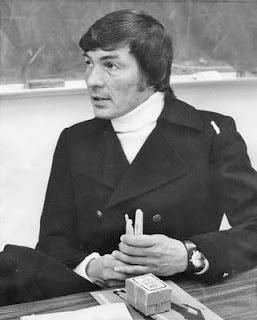 1970s photo of a 30-something white man in a classroom, wearing a white turtlenedk under a dark, double-breasted jacket and holding what looks like some sort of plastic medical instruments