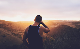 Man looking into the sunset after a workout hike