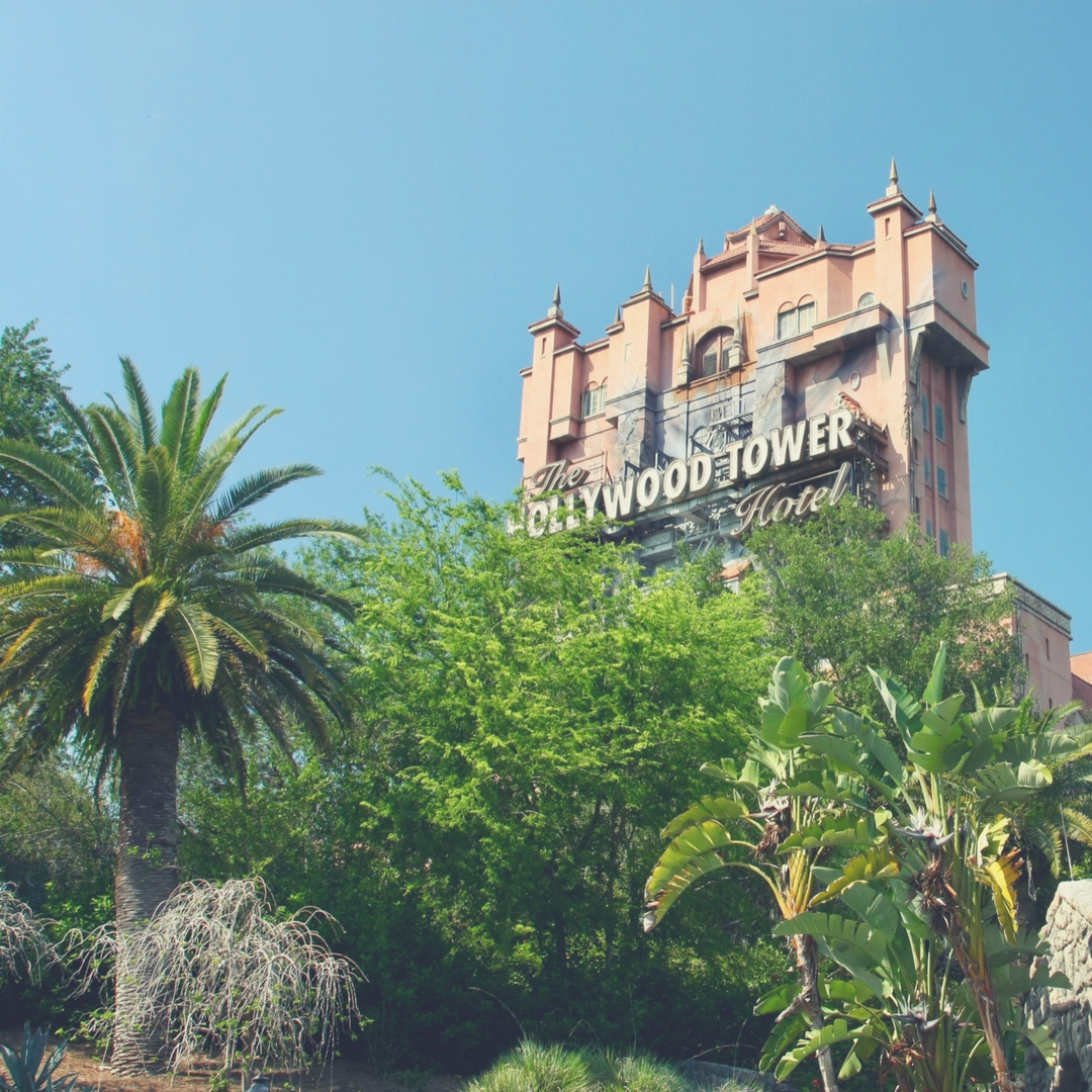 "The camera looks up at the Hollywood Tower of Terror at Disney's Hollywood Studios, Walt Disney World. Trees cover the line of sight to the bottom of the tower, a palm tree sits to the left of the photo. The sun is bright shining down from just off the photo and the sky is a clear blue. Image for ""How to get a much-needed rest at Disney's Hollywood Studios""."
