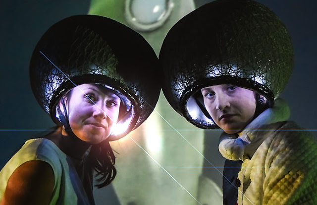 Two women with space helmets on.