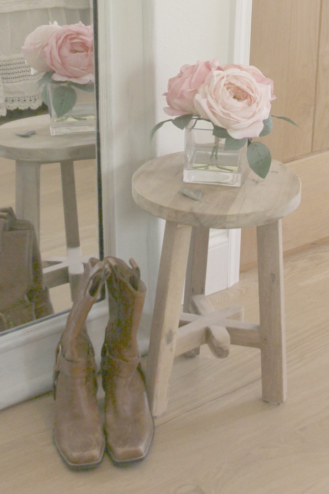 Wood stool with three legs, leather western boots, and white oak wood floor