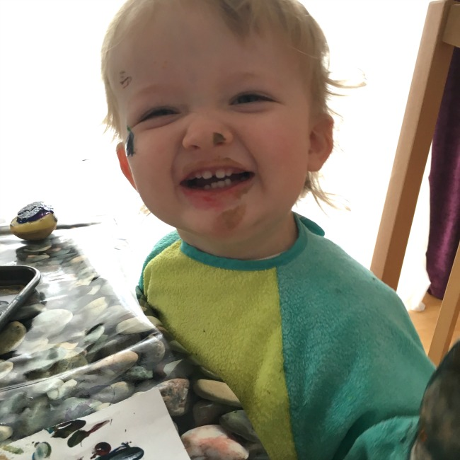 Big smile on toddlers face speckled with splashes of paint