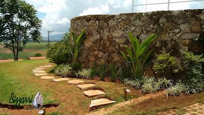 Caminho no jardim com pedra cacão de Carranca com junta de grama com a execução do paisagismo em casa em condomínio em Piracaia-SP.