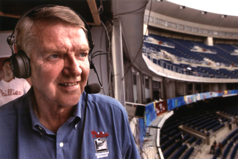 A close-up of Harry Kalas wearing headphones in the broadcast booth of a stadium, looking out at the field