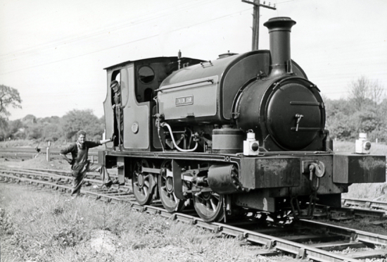 "Photograph of A Hudswell Clarke 0-6-0 Saddletank locomotive, ""London John"" at Marshmoor sidings, owned by John Mowlem Industrial Building Contractors with driver, Nobby Smith, August 1972"