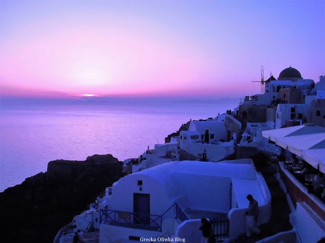 białe greckie domki na tle egejskiego morza i purpurowego zachodu słońca w Fira Santorini na tle purpurowego zachodu słońca