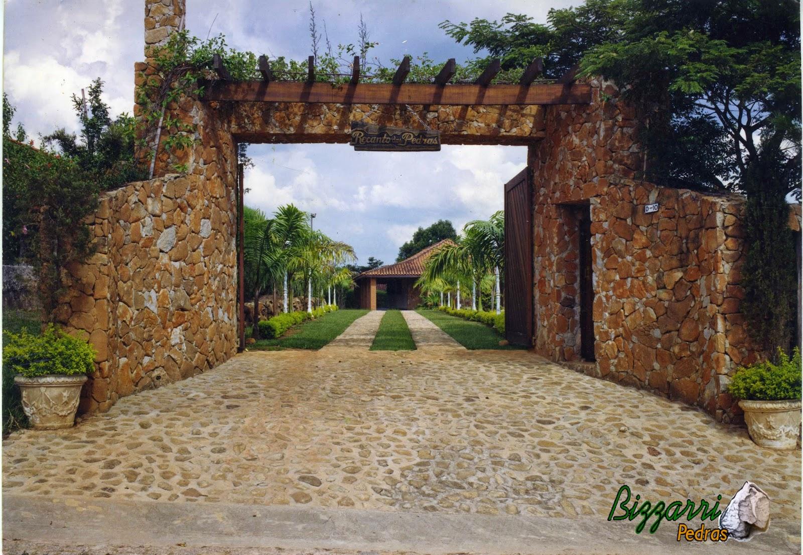Na entrada da residência o calçamento com pedra rústica com os muros de pedra, as paredes de pedra com o pórtico de pedra com execução do paisagismo.