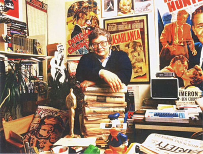Roger Ebert standing with arms rested on a stack of books atop a desk amidst many colorful items and walls covered in film posters