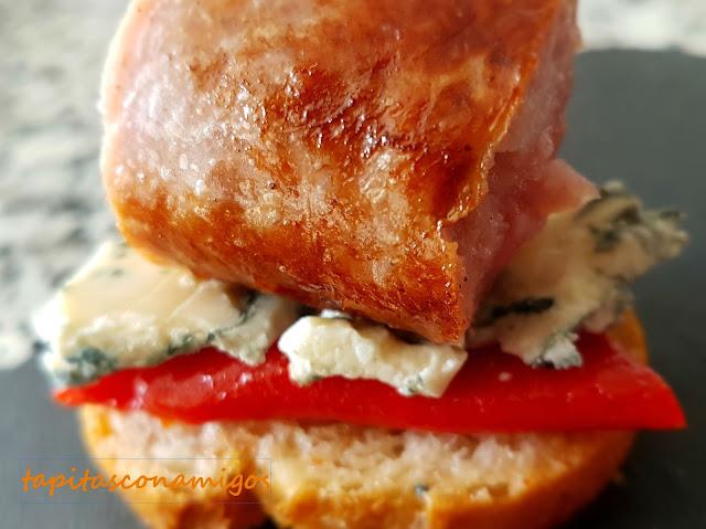Tosta de butifarra, queso azul y piquillos