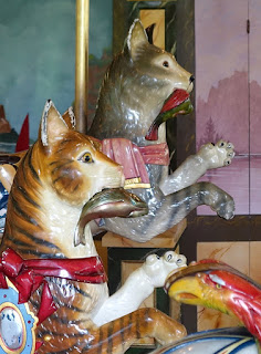 Two domestic cat carousel carvings with fish in their mouths. San Francisco Zoo Carousel.
