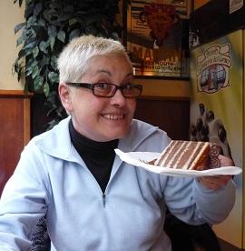 Simpática señora ofreciendo un trozo de pastel