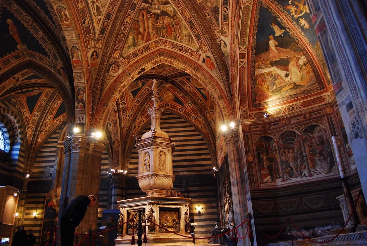 vue d'ensemble du baptistère divisé en une nef et deux bas-côtés. On voit la sculpture en marbre blanc de Jacopo della Quercia qui domine les fonts baptismaux.
