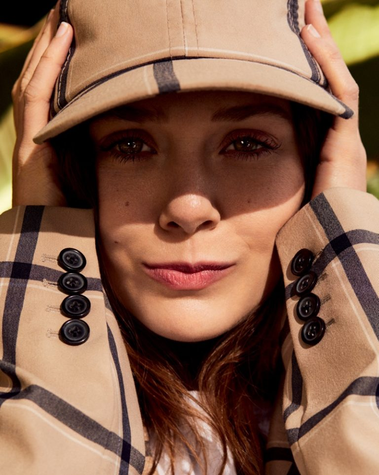 Elizabeth Olsen poses in checkered cap and jacket