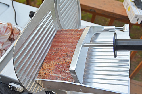 Beswood 250 radial meat and cheese slicer slicing a slab of smoked bacon.