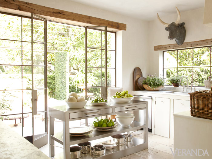 Stunning French Country kitchen with white cabinetry, bull head, steel doors, stainless work island, and design by Pamela Pierce. #FrenchCountry #kitchendesign #kitchendecor #PamelaPierce