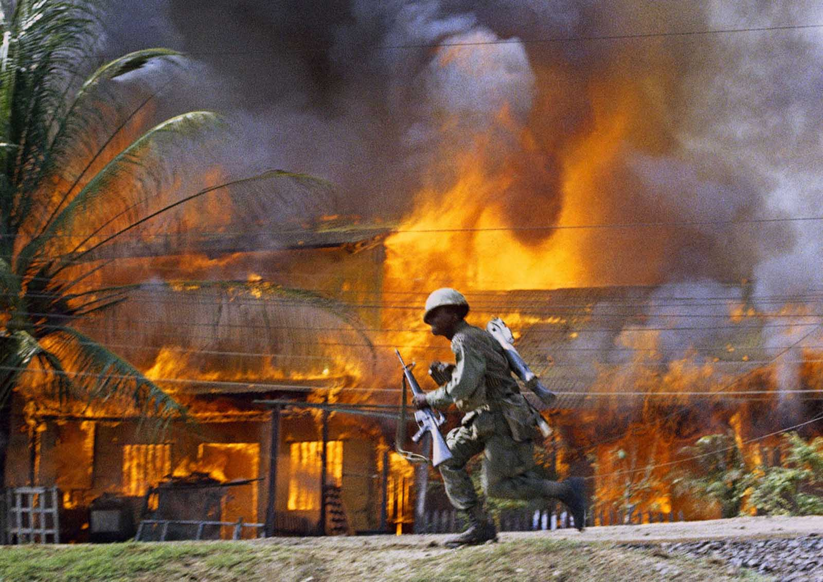 A U.S. trooper runs past a burning building in Saigon in June of 1968.