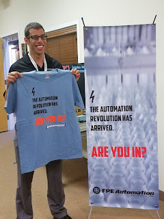 Cognex's Andrew Wassef shows of an FPE automation revolution t-shirt in from of the autommation revolution banner.