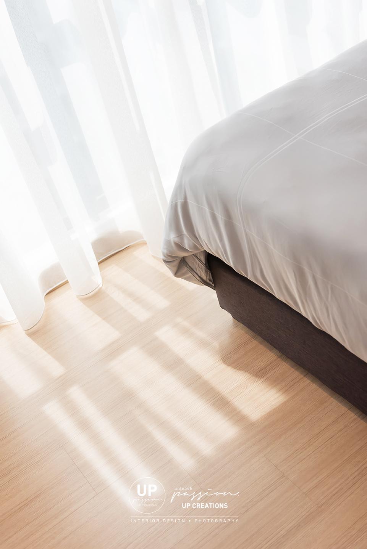 trinity aquata condo master bedroom in wood grain vinyl flooring and sheer curtain with natural light