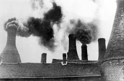 Bottle ovens being fired and creating smoke in The Potteries