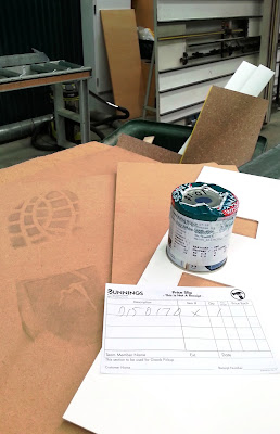 Several pieces of MDF (one with a large boot print on it) and a test pot of paint in front of a bin in a hardware store.