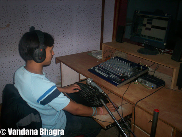 "Community Radio takes wings in Solan : Posted by Vandana Bhagra on www.travellingcamera.com : A novel concept of community radio was started on March 13, 2009 when Himachal's first wireless broadcast was launched by the then chief secretary Asha Swaroop at the MS Panwar Institute of Communication & Management, Shamti, Solan. This broadcast station, more widely known as the ""hamara 90.4 FM"" runs with a punch line of 'subki zuban pe shor, hamara 90.4 Mhz"" radio, which is gaining immense popularity with the local community who are not only sending requests for certain programmes but equally contributing by giving feedbacks as well.Even though community radio is growing rapidly in other states its growth in Himachal has been quite slow as there are not many takers. There are three types of radio systems, one which are government sponsored such as the AIR, second is the private FM radios and third is the community radio which are run by NGO's or educational institutes and are run on nonprofit basis. Communityradio is a radio station owned, run and maintained by a community and in this case it is being run by MSPICM, an educational institute, which is about capitalizing the incredible potential media can offer to engage people and change their lives. Anna FM was India's first campus community radio which was launched on February 1, 2004, by the Education and Multimedia Research Centre and the students of Media Sciences at Anna University produced all the programmes. Other noted CRS include 'Sangham Radio' in Andhra Pradesh, 'TARAgram' in Madhya Pradesh, 'Radio Bundelkhand', Mana Radio in Andhra Pradesh and Raghav FM in Bihar to name a fw.Dr. Brijender Singh Panwar, Director, of MSPICM says that the idea of community radio broadcast came when a Delhi-based NGO, One World South Asia signed a contract with the institute in 2008, to setup the network for the running the station. ""A stretch between Khandaghat to Solan was selected, where in 15 villages on Karol Hill were selected where programmes were to be broadcast nd from these villages itself five reporters were given a chance to run this network. The initial idea was to check the effectiveness of the reach of the programmes and their impact on the local people. For this a time slot of 30 minutes was taken by the All India Radio during which two 15 minutes programmes were aired. A basic stipend was paid to the reporters by the NGO during this period and seeing how successful the run had been the institute applied for the license which helped in starting their own Community Radio after a year in March"".Dr Panwar states, ""Initially a test broadcast was run for one hour in the morning and then one hour in the evening, which was slowly increased to six hours, then twelve and now finally the broadcast time is of 14 hours daily from 7 am to 1 pm and then at 2 pm until 9 pm. The distance covered is 15 kms crow fly radius which covers areas around Solan, parts of Parwanoo, Narag, few areas in Sirmaur district such as Nahan, Saraha, Naina Tikkar, parts in Bilaspur district suh as Arki and Darlaghta to name a few. Areas which come in the line of sight do receive our broadcast. He says this confidently as despite the fact that we are a very small institute and there is no way to actually gauge our reach of programmes, but when we receive calls from our listeners we come to know from which area we get the calls"".      The basic thought behind starting the radio programmes was to involve the people of rural areas where outreach of other means of communication was limited or almost nil. Initiatives were taken to involve the people to suggest programmes, discuss their problems, especially those regarding civic amenities or affecting their day to day lives, and any other issues which could be resolved through voicing them on the radio. Issues covered include health, nutrition, problems of community, sports, local talent, women and child oriented programmes as the main focus of the programmes is to create awareness amongst the local community on employment avenues, hygiene, agriculture,environment, health and women related issues. Health issues such as health tips for senior citizens, tips for reducing maternal mortality rate, nutrition for women during pregnancy, discussion on different health related problems and their remedies are aired frequently.Suman Kashyap, a student from the institute is now employed as a regular with them as after completing her course and due to her exemplary performance she was able to secure a job as a programmer. She says, ""In 2009, I completed a six months course in Radio Jockey from MSPICM and then was absorbed by the Institute for their CR broadcast and this also helped me in pursuing further studies as now I am doing the three years course in Mass Communication"". Hailing from a small village Develi Ki Ser, near Solan, she adds, ""this is a perfect opportunity for me as it helps me financially as well as pursuing further studies. Students from the institute get a number of opportunities as well as hand on training to secure decent jobs when they pass out frm here"". The programming is handled entirely by students who have the liberty of constructing and delivering content which provides exposure to the students and broadens their perception and scope on social problems.Dr Panwar says that to improve the performance of the students and enhance the quality of the programmes we signed a one year contract in 2009 with an NGO, Drishti, who helped in providing content for community linkage as well as sent a master trainer to guide the students. ""Since the start of this broadcast we have been on a very limited budget and on a self help basis as we did not receive any monetary grant from the government or advertisements from the DAVP. It was only after November, 2010 that we have started receiving advertisements from local people and few educational institutes due to the increasing popularity of the broadcast and manage to cover the five minute slot per hour for advertisements, which has helped in some kind of revenue generation. Our monthly expenditure including contet, salaries, running cost and variables come to about 75,000 to around one lakh but still efforts are on to run this programme successfully"". Dr Panwar proudly adds that their institute was among the two CRS educational establishments selected by a team of UNESCO to be surveyed for its outreach and effect. The other being the University of Mumbai who broadcasts for 12 hours, theirs being the longest for 14 hours. Since the content of the programmes is in the hands of the community this team of four members and students from the institute travelled to various villages to talk to the villagers and get their feedback and reactions to the programmes aired.For a promising future to the students at the institute Dr Panwar hopes that practical training, help in content generation, interaction with rural folk, scripting and editing will help the students secure good jobs as there is immense talent in Himachal and he wishes to nurture them and bring about a change by his small but selfless effort."