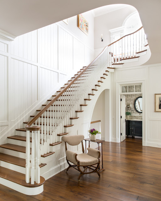 Magnificent staircase, walnut floors, and paneled wall in traditional home by Giannetti Home