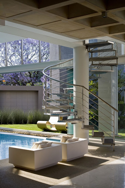Photo of spiral staircase by the pool with two sofas in front