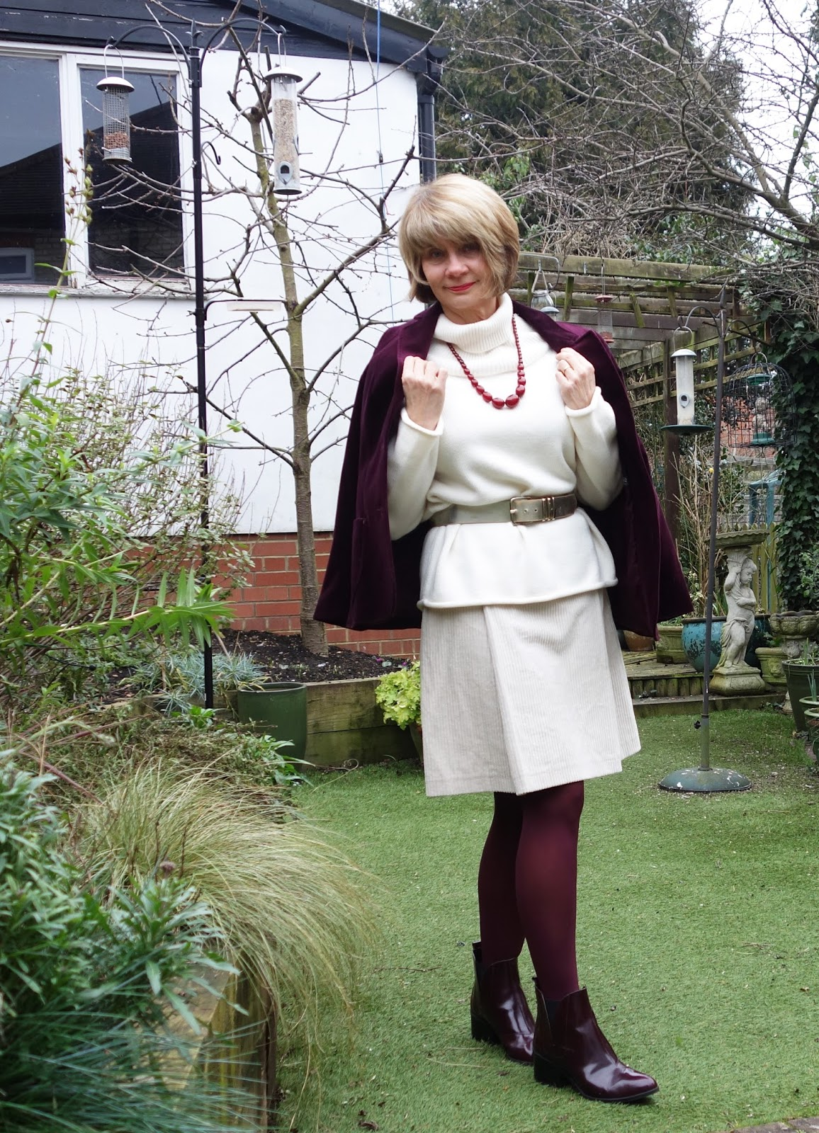 Burgundy velvet jacket worn with cream skirt and jumper and burgundy accessories