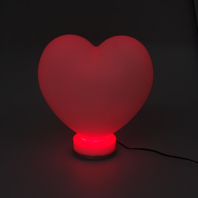 Imagem mostra luminária de coração acesa na cor vermelha