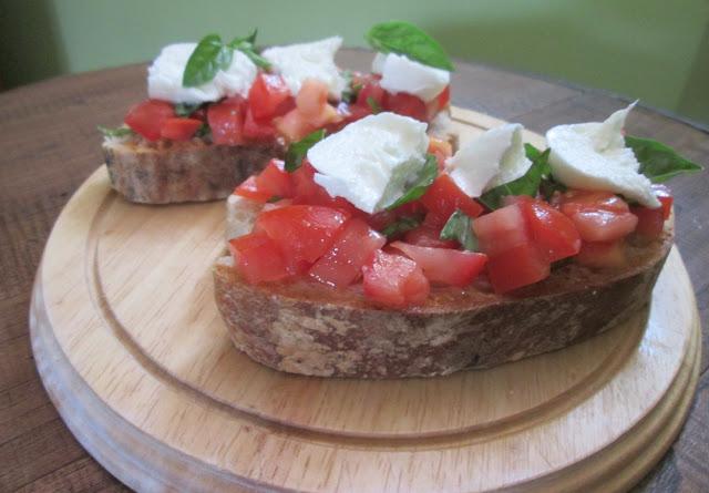 taboa redonda servindo bruschetta de tomate e mozzarella