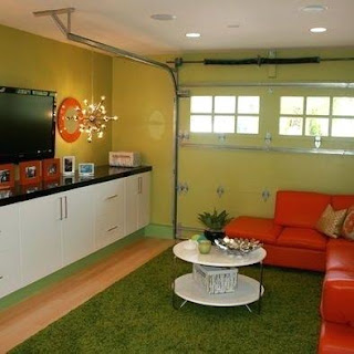 An image of a garage converted to a living room with red couches and TV