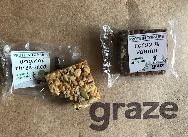 Small individual wrapped flapjacks one (cocoa & vanilla) in it's packet, the other (original three-seed) has a bite out of it. They are both displayed on a brown cardboard box saying graze