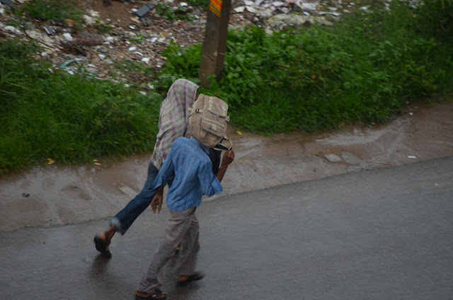 kids with school bag on head running in Monsoon