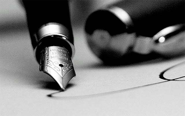 Pluma escribiendo sobre página en blanco