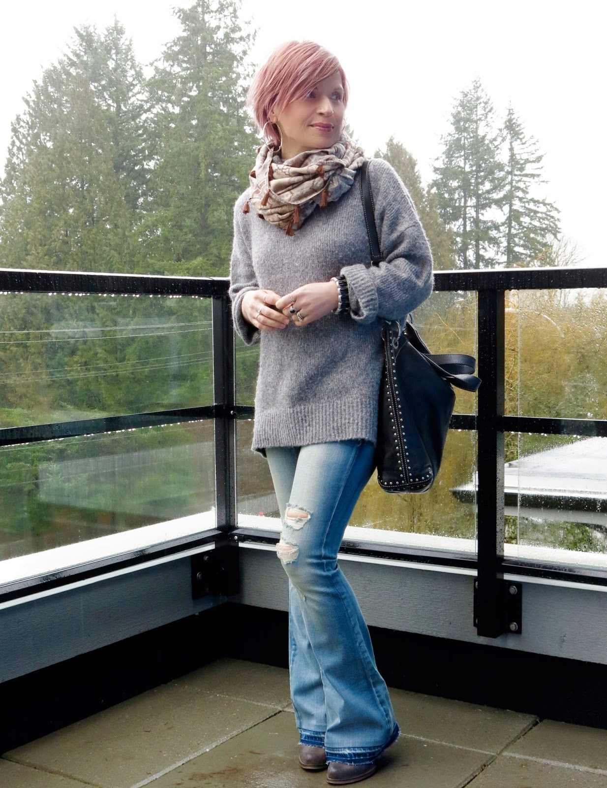 styling distressed flare jeans with a woolly turtleneck and tassel-embellished scarf