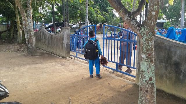 TERLAMBAT : Seorang anak nyaris tidak diizinkan masuk ke dalam sebuah di daerah Kubu Raya, karena sang anak datang terlambat saat apel bendera sedang berlangsung.  Foto Asep Haryono