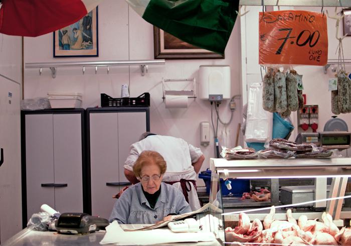 une femme lit un journal tandis qu'un homme découpe de la viande de volaille