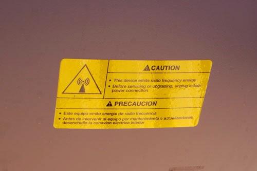 Foto de etiqueta no verso da antena dizendo : Este equipamento emite energia de rádio frequência, antes de efetuar manutenção, desligue-o da energia elétrica.