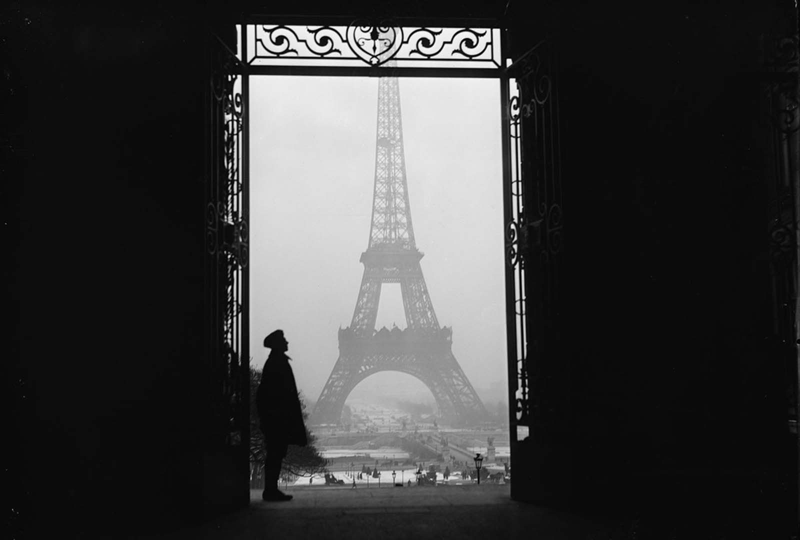 An American soldier stands in the doorway of an apartment house before the Eiffel Tower in March of 1919.