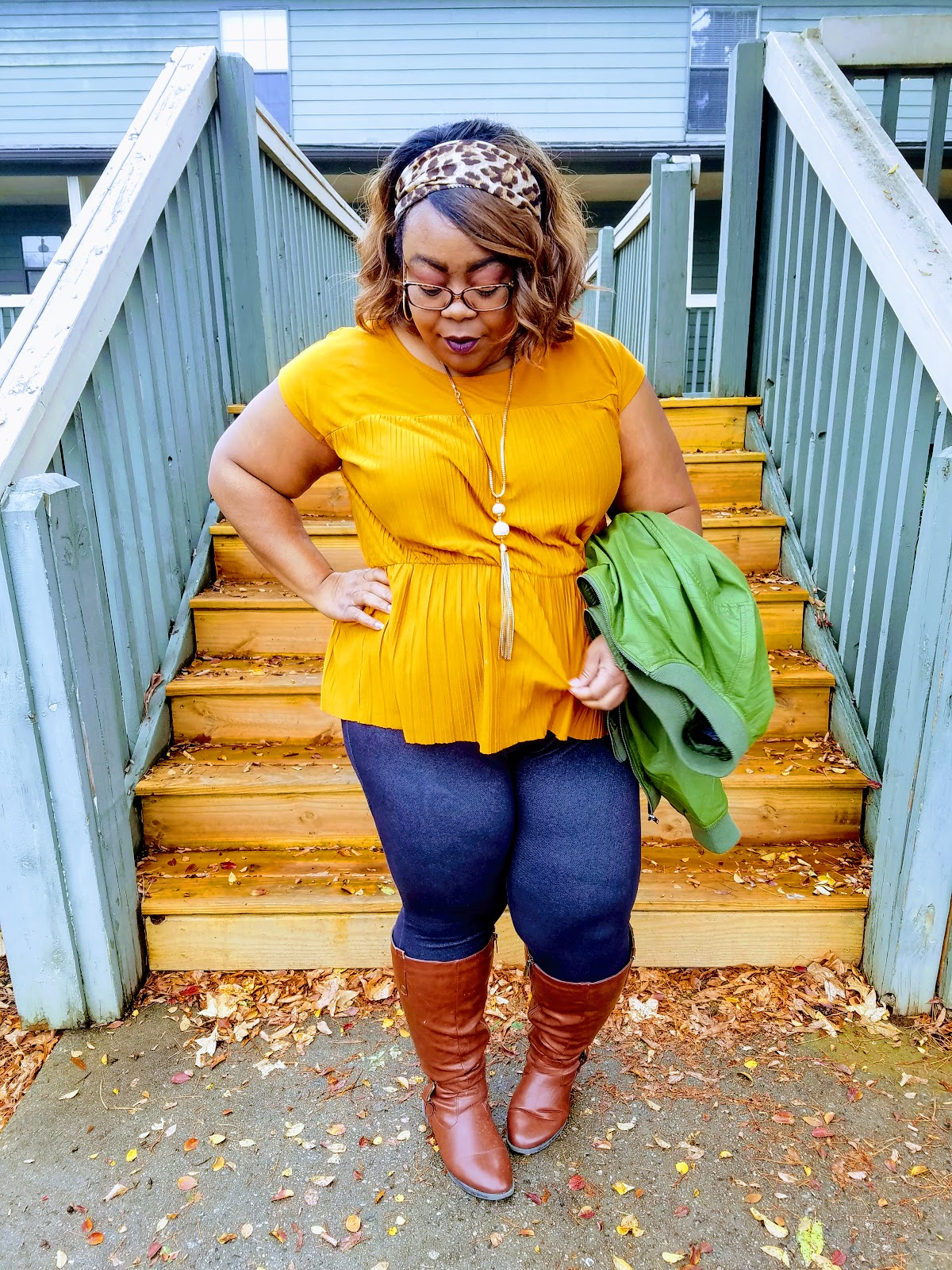 mustard blouse, green bomber jacket, denim jeggings, cognac boots, leopard print headband, gold tassel necklace