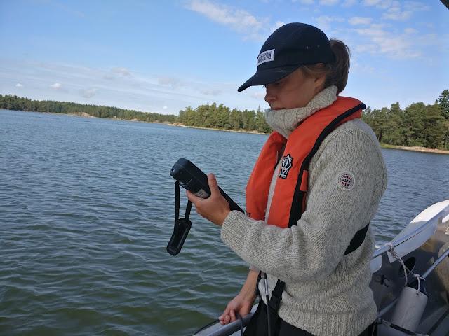 Henkilö veneessä katsoo mittaria.